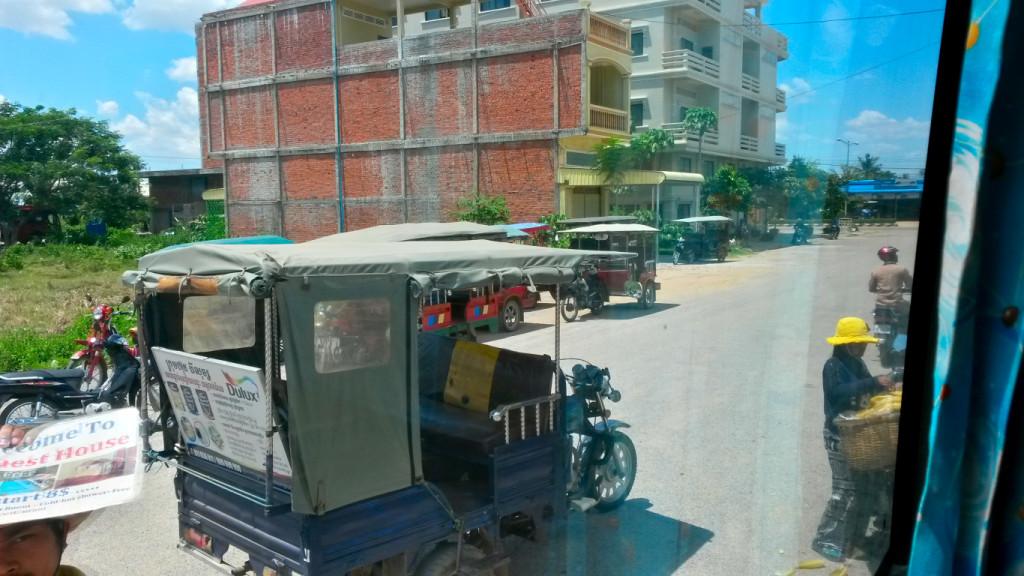 Wartebde Tuk Tuks vor dem Bus